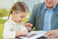 Cute granddaughter attentively exploring a book. stock image