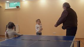Granddaughter gives her grandfather a ball near the tennis table, and he is preparing to make the first blow. Slow stock footage