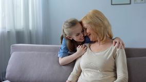 Cute granddaughter giving gift to grandmother and hugging her, family love. Stock photo royalty free stock images