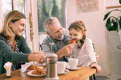 Cute granddaughter with nice hairstyle trying delicious croissant royalty free stock photo