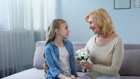 Cute granddaughter presenting bouquet of chamomiles to grandmother, birthday royalty free stock photography
