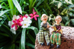 Cute grandfather and grandmother ceramic dolls sitting on the la Stock Photos