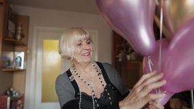 Cute grandma celebrates her birthday. Holds multicolored balloons in her hands stock video footage