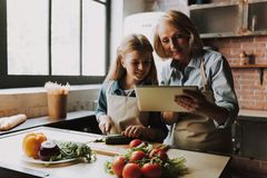 Cute Grandma and Granddaughter Cutting Vegetables stock photography