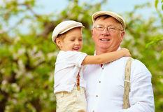Cute grandpa with grandson on hands in spring garden Royalty Free Stock Photos