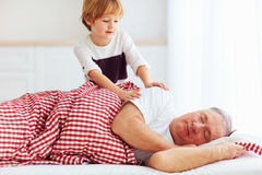 Cute grandson gently wakes hid grandpa up Stock Photography