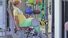 Cute granny trains her legs in the gym on training apparatus. Senior woman sits on training apparatus in the gym. Elderly woman is training her legs and shows stock footage