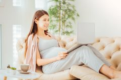 Cute gravid woman lying and using the laptop. Have a rest. Young cute gravid woman lying in the bright room on the sofa smiling and using the laptop Royalty Free Stock Image