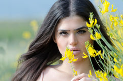 Cute Greek model standing behind of yellow bush Royalty Free Stock Photography