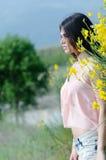 Cute Greek model standing behind of yellow bush Stock Photo