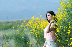 Cute Greek model standing behind of yellow bush Royalty Free Stock Images