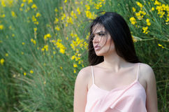 Cute model standing front of yellow bush Royalty Free Stock Photo