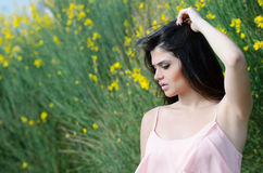 Cute Greek model standing front of yellow bush Royalty Free Stock Photos