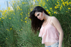 Cute Greek model standing front of yellow bush Stock Images