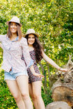 Cute grils walking on a trunk Stock Images