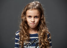 Cute grimacing girl in a blue shirt. Portrait of a cute grimacing girl in a blue shirt, gray background Stock Photography