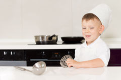 Cute grinning little boy in a chefs hat and apron Stock Photo