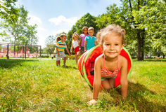 Cute group of kids play crawling in tube Royalty Free Stock Photos