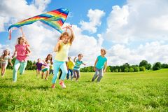 Cute group of kids run with kite Stock Image