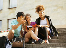 Cute group of teenages at the building of university with books huggings, back to school Stock Image