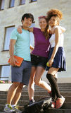 Cute group of teenages at the building of university with books huggings, back to school Royalty Free Stock Photos