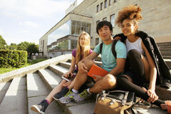 Cute group of teenages at the building of university with books huggings, back to school Royalty Free Stock Photo