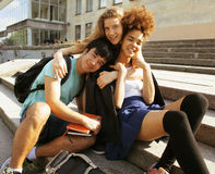 Cute group of teenages at the building of university with books huggings, back to school Stock Photos