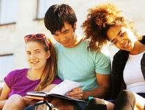 Cute group of teenages at the building of university with books huggings Stock Images