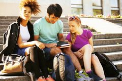 Cute group of teenages at the building of university with books huggings, diversity nations Royalty Free Stock Photo