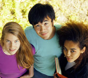 Cute group of teenages at the building of university with books huggings, diversity nations Royalty Free Stock Photos