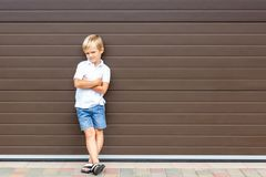 Cute grumpy blond child in casual clothing standing against brown garage door. Angry kid boy with crossed arms near house.Awkward stock images