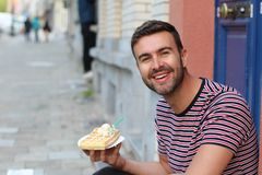 Cute guy eating a waffle in Brussels, Belgium.  stock images