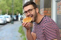Cute guy eating a waffle in Brussels, Belgium.  royalty free stock photos