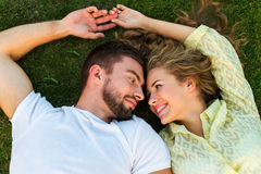 Cute guy and girl lie on the grass. Stock Images