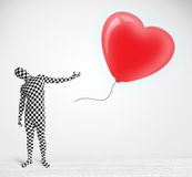 Cute guy in morpsuit body suit looking at a balloon shaped heart Stock Image
