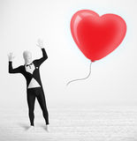 Cute guy in morpsuit body suit looking at a balloon shaped heart Royalty Free Stock Images