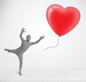 Cute guy in morpsuit body suit looking at a balloon shaped heart Royalty Free Stock Photos