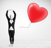 Cute guy in morpsuit body suit looking at a balloon shaped heart Royalty Free Stock Photography