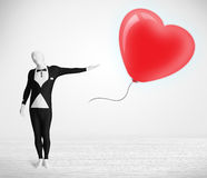 Cute guy in morpsuit body suit looking at a balloon shaped heart Royalty Free Stock Image