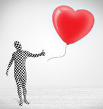 Cute guy in morpsuit body suit looking at a balloon shaped heart Stock Photo