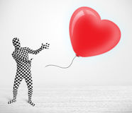 Cute guy in morpsuit body suit looking at a balloon shaped heart Stock Images