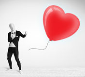 Cute guy in morpsuit body suit looking at a balloon shaped heart Royalty Free Stock Photo