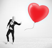 Cute guy in morpsuit body suit looking at a balloon shaped heart Stock Photography