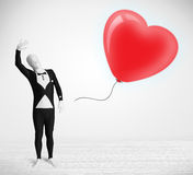 Cute guy in morpsuit body suit looking at a balloon shaped heart Stock Photos