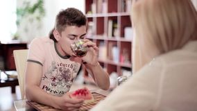 Cute guy sits at table in front of blonde woman, drinks tea and eats watermelon stock video