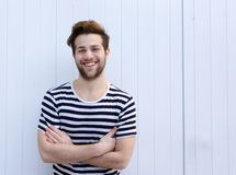 Cute guy smiling with arms crossed on white background Stock Photo