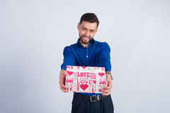 Cute guy smiling holds gift Stock Photos