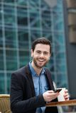 Cute guy smiling with mobile phone Royalty Free Stock Photos