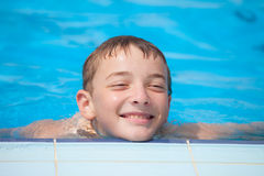 Cute guy smiling in the pool. Summer day Royalty Free Stock Photo