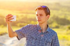 Cute guy takes a selfie on the phone in the sun stock photo